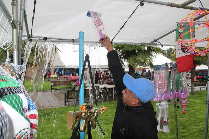 PMG PHOTO: JUSTIN MUCH - Keeping the water off the tarp tops, and hunkering down to stay dry, were key activities Sunday at The Plaza in downtown Woodburn as folks celebrated day 1 of Hispanic Heritage Month.