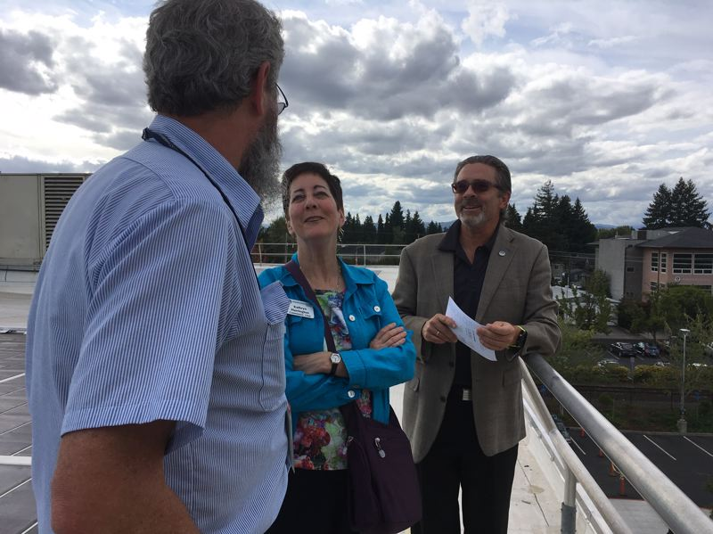 PMG PHOTO BY PETER WONG - Board Chairwoman Kathryn Harrington and Martin Granum, the county's facilities manager, listen to Mark Epling, general supervising electrician, on the rooftop of the newly retrofitted Public Services Building in Hillsboro.