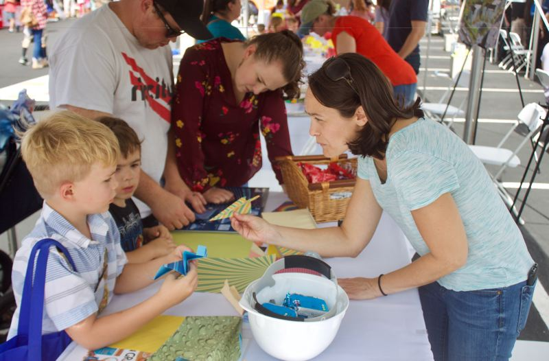 PMG PHOTO: CHRISTOPHER KEIZUR - Erika Fitzgerald made paper airplanes during CityFest in honor of Boeing.