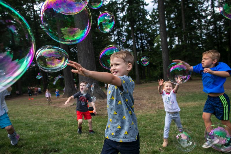 PMG PHOTO: JAIME VALDEZ - Ezra McCreith, 5, and his sister, Cora,3, (White shirt), chase after bubbles during the Trillium Creek Primary's Backyard BBQ Friday, Sept. 13.