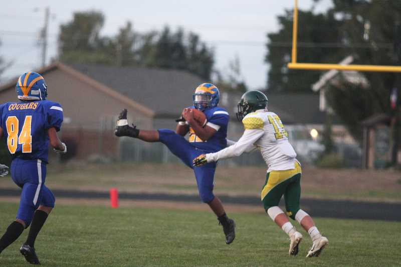 PMG PHOTO: PHIL HAWKINS - Junior Damien Tavera pulls down an interception to stop Gastons opening drive and helped keep the Greyhounds scoreless through the first half of the Cougars home-opener.