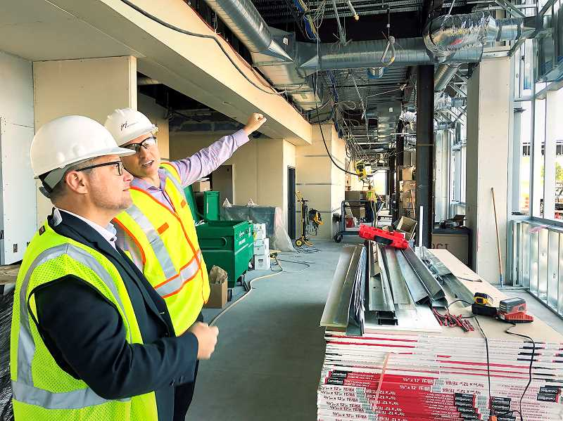 PMG PHOTO - Contractors examine the progress in construction of the annex to the Providence Newberg Medical Center.