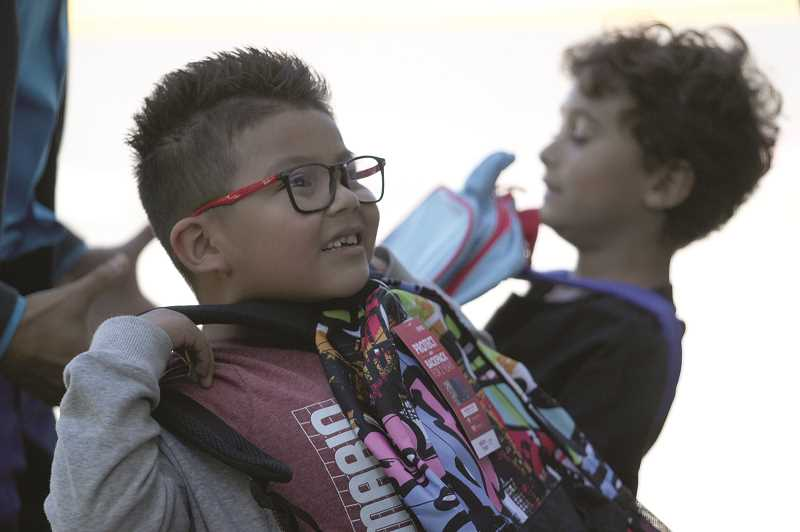 PMG PHOTO: PHIL HAWKINS - Nellie Muir Elementary student Anthony Martinez holds up one of 117 backpacks donated to area schools by Salem Health on Thursday.