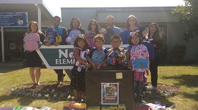 PMG PHOTO: PHIL HAWKINS - Representatives of Salem Health, along with members of Nellie Muir Elementary School display the school supplies delivered on Thursday. Front Row: students Jaquelyn Lopez, Tobin Saucedo, Anthony Martinez and Claudia Silva.