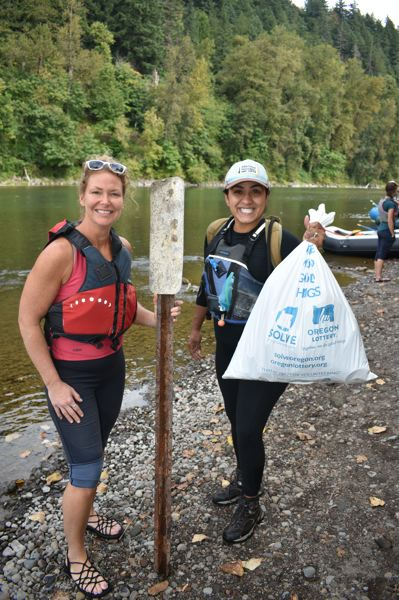 PMG PHOTO: SHANNON O. WELLS - Cindy Kolomechuk and a fellow Sandy River Cleanup participant collected items including a highway marker pole and a full bag of garbage during the cleanup on Saturday.