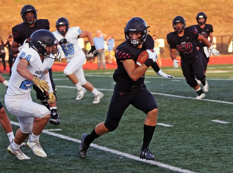 PMG PHOTO: DAN BROOD - Tualatin High School senior Luke Marion, shown here in the Wolves' first game of the season, had both an interception return and reception for a touchdown in the 32-13 win over Oregon City.