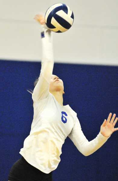 GRAPHIC PHOTO: GARY ALLEN - Junior outside hitter Brynna Geibel gets a mitt on the ball during Newberg's 3-0 win over Liberty.
