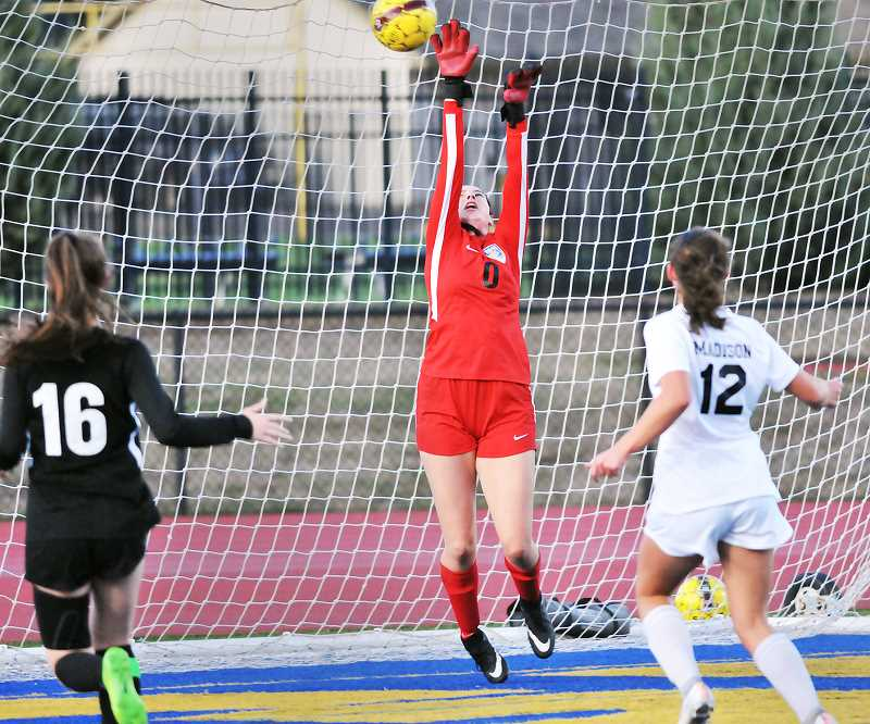 GRAPHIC PHOTO: GARY ALLEN - Senior goalkeeper Ashleigh Rickert goes up to stop a shot versus Madison last week at home.