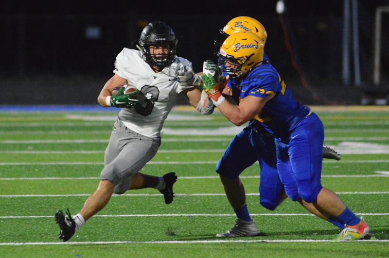 PMG PHOTO: DAVID BALL - Tigard High School senior running back Hunter Gilbert (left) tries to get a way from a pair of Barlow defenders during the Tigers' road victory on Friday.