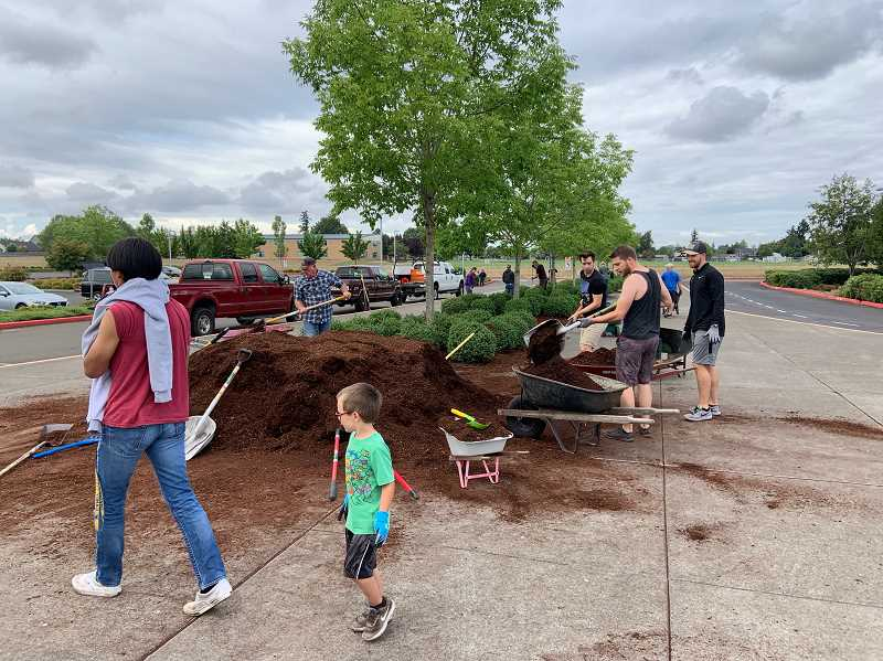 COURTESY PHOTO: JENNIFER TURNER - Volunteers from Christ the King Community Church spruce up the grounds at Baker Prairie Middle School on Aug. 11.