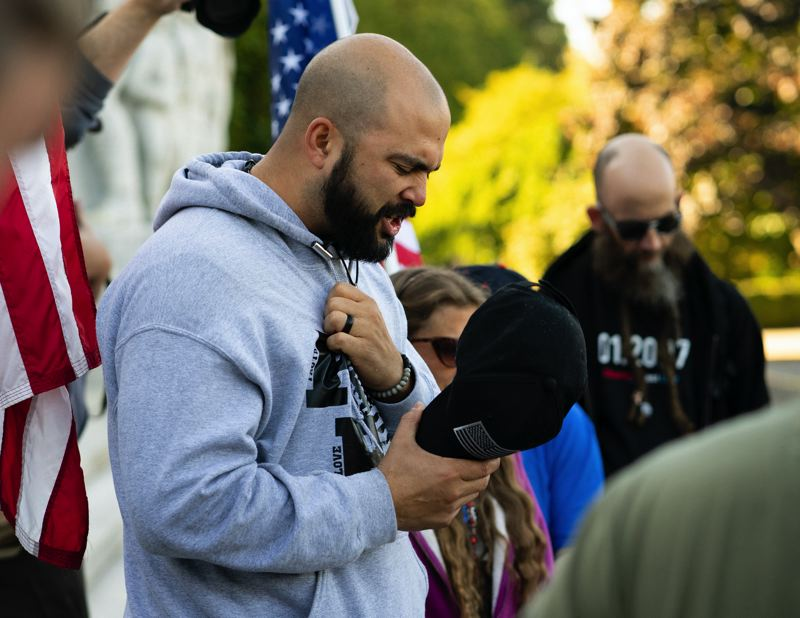 PMG PHOTO: KIT MACAVOY - Joey Gibson leads supporters in prayer on the steps of the Capitol Building in Salem, following the conclusion of a flag-waving rally in October 2017. Gibson, the leader of Patriot Prayer, is extremely active on social media, where he has attracted a large following.
