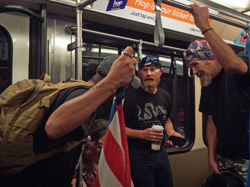PMG PHOTO: KIT MACAVOY - Russell Schultz (center) and fellow Patriot Prayer members ride the MAX train into downtown Portland to attend a rally in late June 2019.