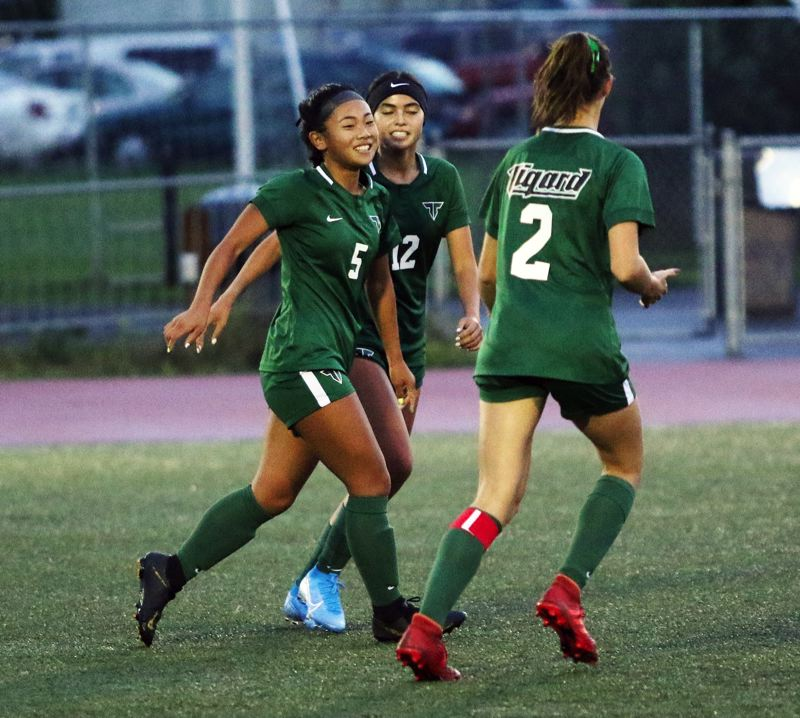 PMG PHOTO: DAN BROOD - Tigard freshman Jaiden Riodil (5), next to senior Kristiana Saldana (12) and junior Lydia Emory, smiles after scoring the second of her four goals in the Tigers' 4-0 win over Franklin.