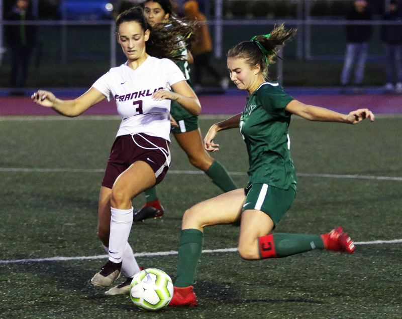 PMG PHOTO: DAN BROOD - Tigard High School junior Lydia Emory (right) looks to boot the ball past Franklin senior Sylvia Goldrich-Middaugh during Tuesday's non-league match.