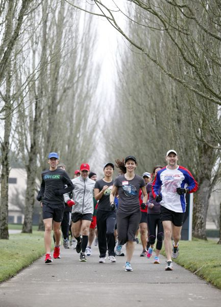 PMG FILE PHOTO: JONATHAN HOUSE - A group of volunteer coaches for Portland Fit get charged up in a marathon training season with a Saturday morning run on the Fanno Creek Trail in 2013.