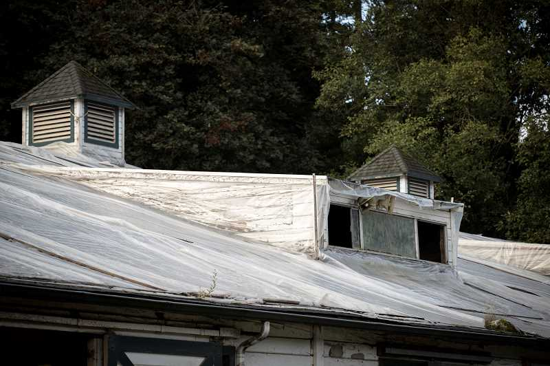 PMG PHOTOS: JAIME VALDEZ - Tarps provide cover from rainwater to the roof of Lake Oswego Hunt Club.