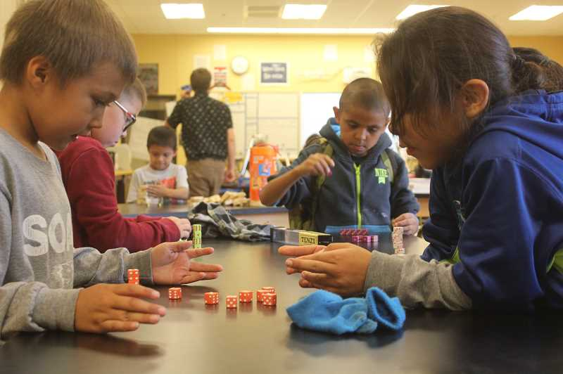 DESIREE BERGSTROM/MADRAS PIONEER - In the foreground, Keadyn Jensen, left, plays a dice game with JoeRay Stwyer during one of the hourlong sessions of the new partnered afterschool program at WSK8. In the background, Orrin Cortazar and Phillip Winishut-Boise also play the dice game. One of the session choices for students on Monday was board games with teacher, Andrew Jackson.