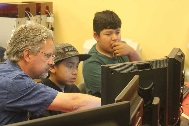 DESIREE BERGSTROM/MADRAS PIONEER - Teacher Brian Gallagher helps student Declan Parton problem solve an issue on his computer, while Luis Tellez watches. The computer class is a part of the afterschool program.