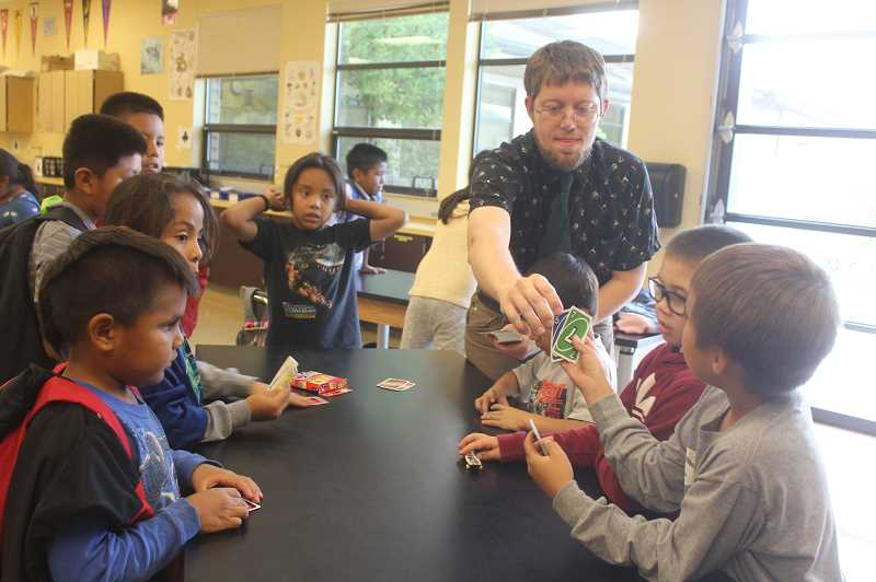 DESIREE BERGSTROM/MADRAS PIONEER - Teacher Andrew Jackson instructs a group of afterschool program students on how to play the popular card game 'UNO.'