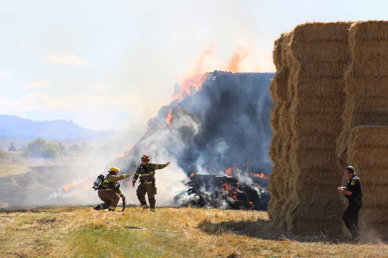 HOLLY M. GILL/MADRAS PIONEER - Crews from the Jefferson County Fire District No. 1 work to douse a haystack fire on Southwest Birch Lane on Sept. 11. It was the second major hay fire in the district in less than a week.