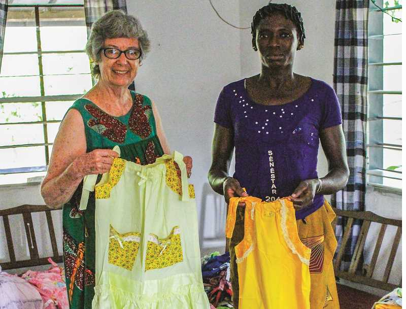 PHOTO COURTESY OF LINDA SHARP - Linda Sharp, left, with one of the women from the village of Ferkessedougou, in Côte d'lvoire Africa. They are showing some of the pillow case dresses that came from Prineville. Mary Reed originally started the project, which has steadily grown, to help the children in the village.