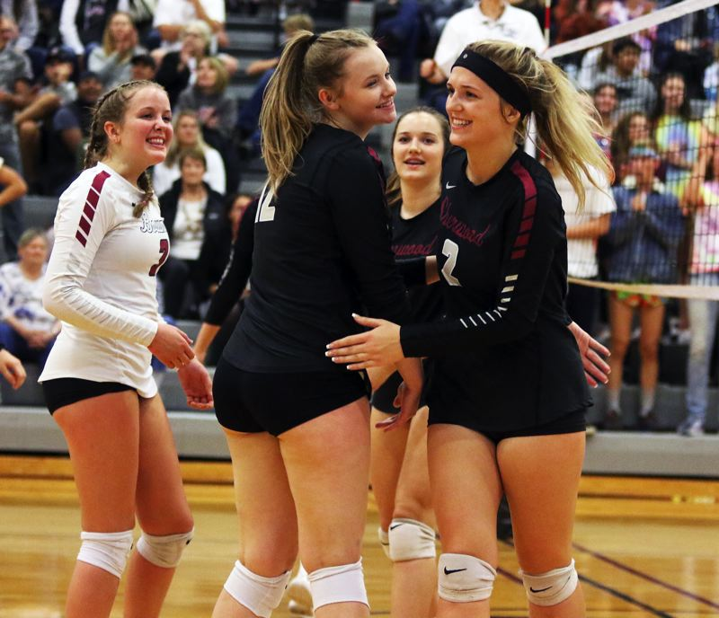 PMG PHOTO: DAN BROOD - Sherwood players, including Piper Harrop (3), Evan Parent Korsness (12) and Allison Fiarito (2) are all smiles during the fourth set of the Lady Bowmen's win over Newberg.