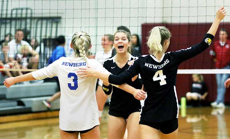 TIGARD TIMES PHOTO: DAN BROOD - Newberg's (from left) Kaylie Duckworth, Tori Petersen and Lauren Griswold celebrate after scoring a point in the first set of the Tigers' match at Sherwood on Sept. 18.