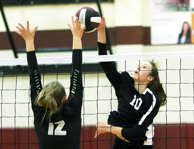 TIGARD TIIMES PHOTO: DAN BROOD - Newberg freshman outside hitter Sophia Gregoire-Salagean attempts to drive the ball past Sherwood senior Evan Parent-Korsness during the Sept. 18 match at Sherwood High School.