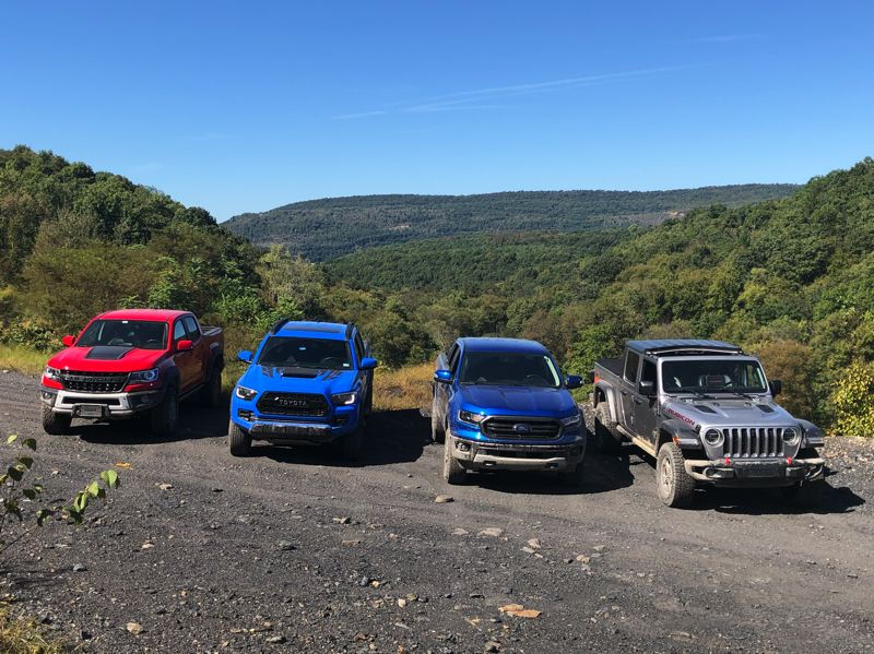 PMG PHOTO: JEFF ZURSCHMEIDE - This is a great time to consider buying a serious off-road midsize pickup. The choices (from left) including the 2019 Chevrolet Colorado ZR2 Bison, the 2019 Toyota Tacoma TRD Pro, the 2019 Ford Ranger FX4, and the 2020 Jeep Gladiator Rubicon.