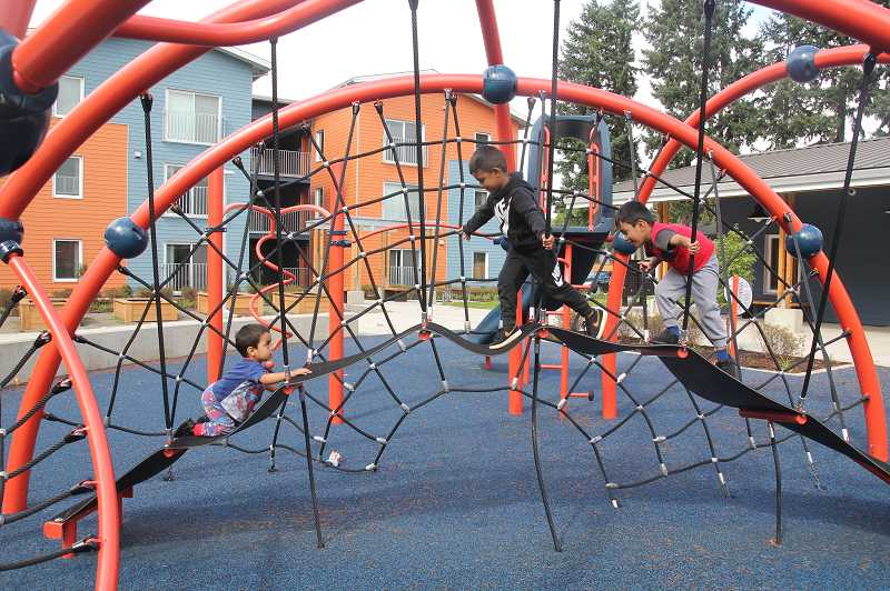 PMG PHOTO: JUSTIN MUCH - Youngsters enjoy a climb on the playground equipment at the new Colonia Unidad apartments, a Farmworker Housing Development Corporation complex in Woodburn.