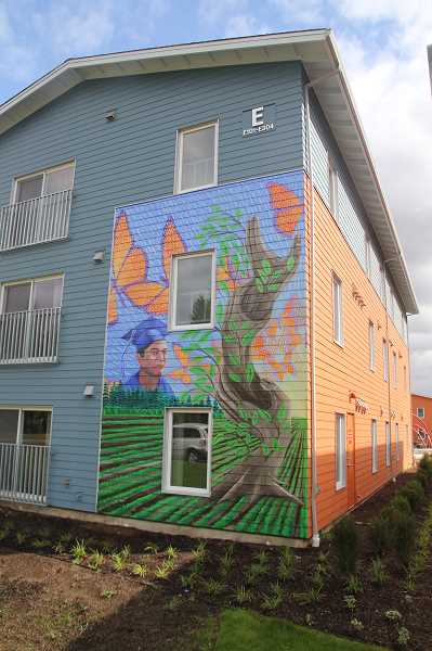 PMG PHOTO: JUSTIN MUCH - Murals at the new Colonia Unidad apartments, a Farmworker Housing Development Corporation complex in Woodburn, depict the hands that build a community, education the bolsters it and butterflies that symbolize the transition of its growth.