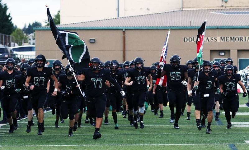 PMG PHOTO: DAN BROOD - The Tigard High School football team takes the field prior to the Tigers' Three Rivers League opener with Canby on Friday.