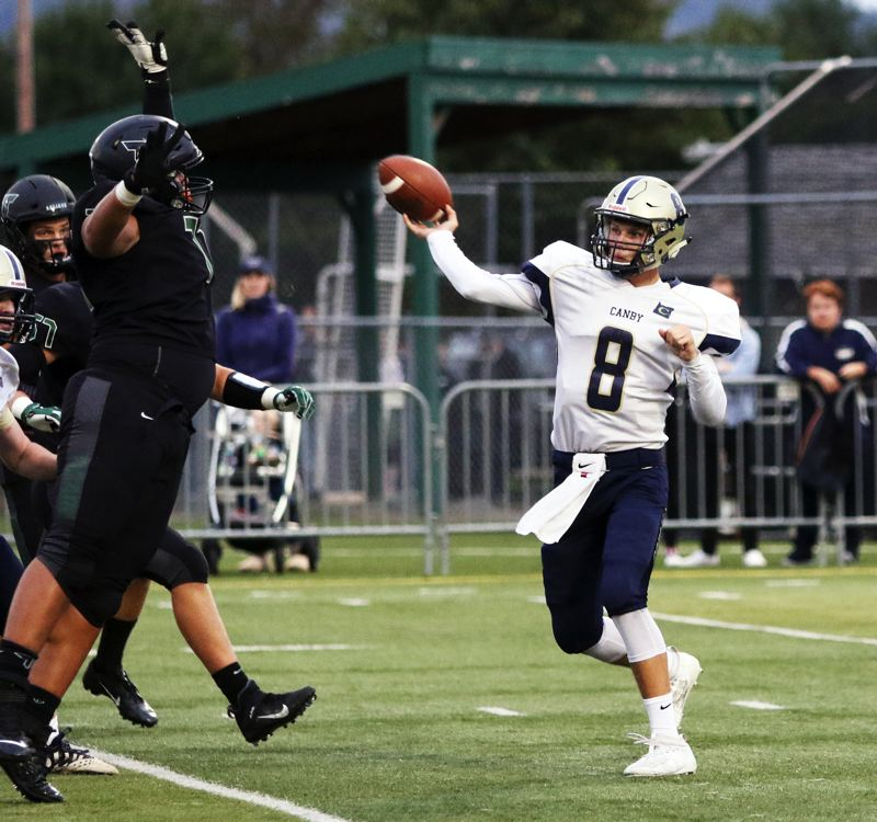 PMG PHOTO: DAN BROOD - Canby High School senior quarterback Andrew Peters (right) throws a pass during the Cougars' Three Rivers League game at Tigard.
