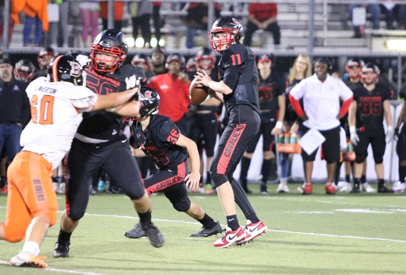 PMG PHOTO: JIM BESEDA - Clackamas quarterback Austin Atkeson threw for 261 yards and four touchdowns, and rushed for another 50 yards on 10 carries, leading the Cavaliers to a 39-19 home win Friday over Beaverton.