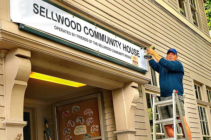 DAVID F. ASHTON - Making the buildings name change official, volunteer Bob Burkholder - a SMILE Board Member - put up the new Sellwood Community House sign over the front door.
