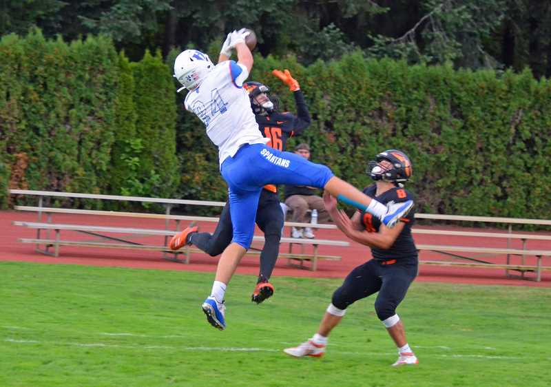 PMG PHOTO: JOHN BREWINGTON - Hillsboro's Nate Smith goes up for a ball over two Scappoose defenders during the Spartans' game with the Indians last Friday, Sept. 20, at Scappoose High School.