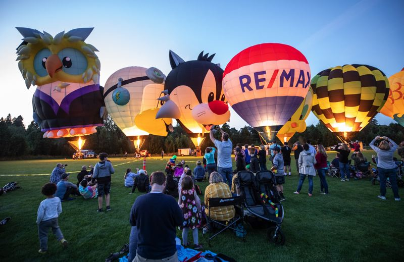 PMG PHOTO: JONATHAN HOUSE - Festivalgoers enjoy balloons lit up agaist an evening sky during the Night Glow of Tigard's Festival of Balloons, one of Washington County's annual tourism draws.