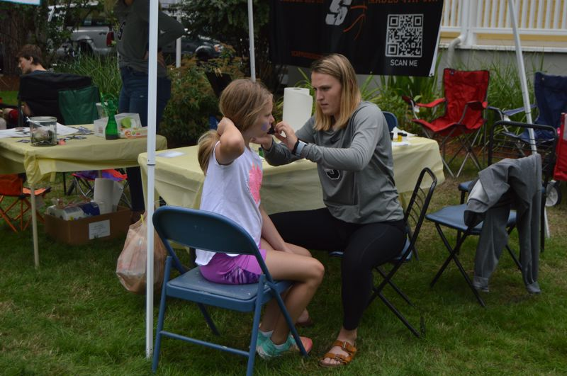 PMG PHOTO: NICOLE THILL-PACHECO - Kaitlin Dahla carefully paints the letters BFF on the cheek of 10-year-old Samanth Lampman. Members of the Scappoose Youth Basketball program were offering face painting as a fundraiser during the event.