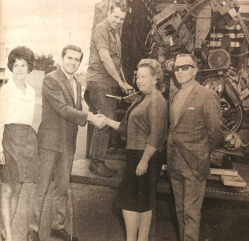 CENTRAL OREGONIAN - SEPTEMBER 25, 1969: Mrs. Doris Boyd is pictured handing the keys to the Central Oregonian to the new president of Central Oregonian Publishers, Inc., Dennis A. Smith, on his assumption of operation of the newspaper. Pictured left to right, are Mrs. Dennis (Kathleen) Smith, Dennis, Norman Donnelly, Doris and Dave Boyd. ackground is a linotype which has been replaced by new cold type equipment.