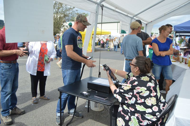 PMG PHOTO: NICOLE THILL-PACHECO - Sen. Betsy Johnson, D-Scappoose, helps a customer at the Scappoose Community Club's booth where volunteers were selling the famous Scappoose Sandwiches.