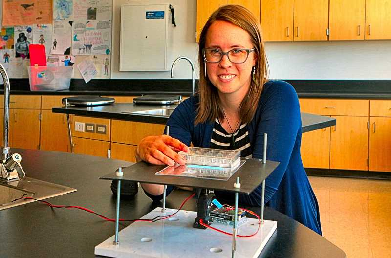 DAVID F. ASHTON - Nationally-honored Franklin High School science teacher Anne McHugh shows a student-built laser fluorometer - made in collaboration with NASA - to digitally count cells in a sample.