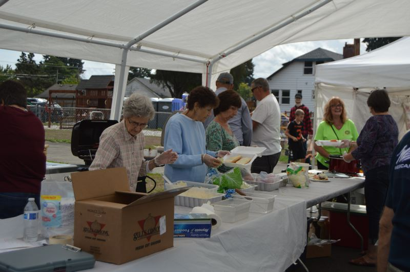 PMG PHOTO: NICOLE THILL-PACHECO - Volunteers with the Scappoose Community Club help prepare plates of food for customers during the Sauerkraut Festival.