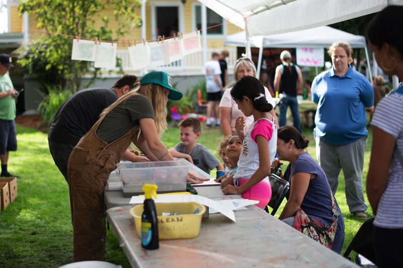 PMG PHOTO: ANNA DEL SAVIO - Jenna Reineking and Nick Patton, Tumblewheel Studios co-founders, lead participants in themed art projects at the Sauerkraut Festival. The arts nonprofit led different projects throughout the day, including making faces on cabbage heads and printmaking.