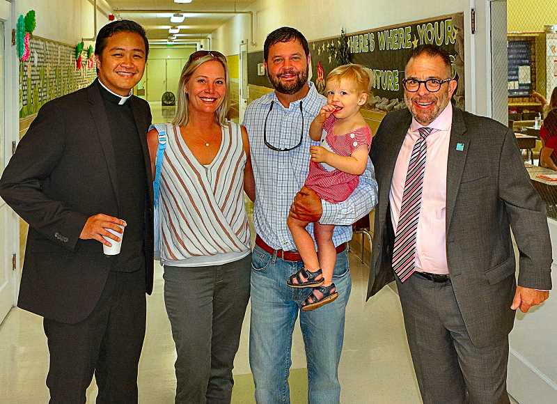 DAVID F. ASHTON - Here, in the opening moments of the first day of the new year at Holy Family Catholic School, was the parishs Fr. Rodel Demesa, left, meeting the Musey family - with new Principal Joe Galati at right.