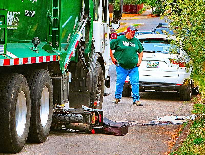 DAVID F. ASHTON - Considering how the motorcycle was wedged under the garbage truck, its rider was very lucky indeed not to have been very much more severely hurt.