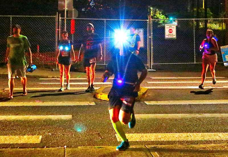 DAVID F. ASHTON - After taking a detour through the Ardenwald-Johnson Creek neighborhood, Hood-to-Coast Relay Race runners - many wearing lamps, to guide them in the predawn darkness - head across Johnson Creek Boulevard to continue their jog toward Portland on the Springwater Corridor Trail.