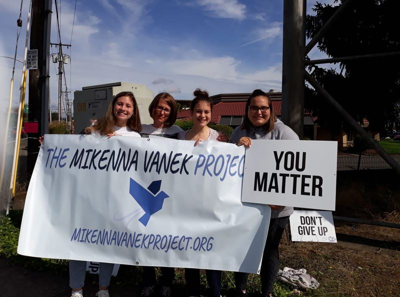COURTESY PHOTO - Mikenna Vanek Project members and volunteers Genae Vanek (from left), Tabitha Williams, Gabrielle Vanek and Liberty McCarthy wave signs in Oregon City.