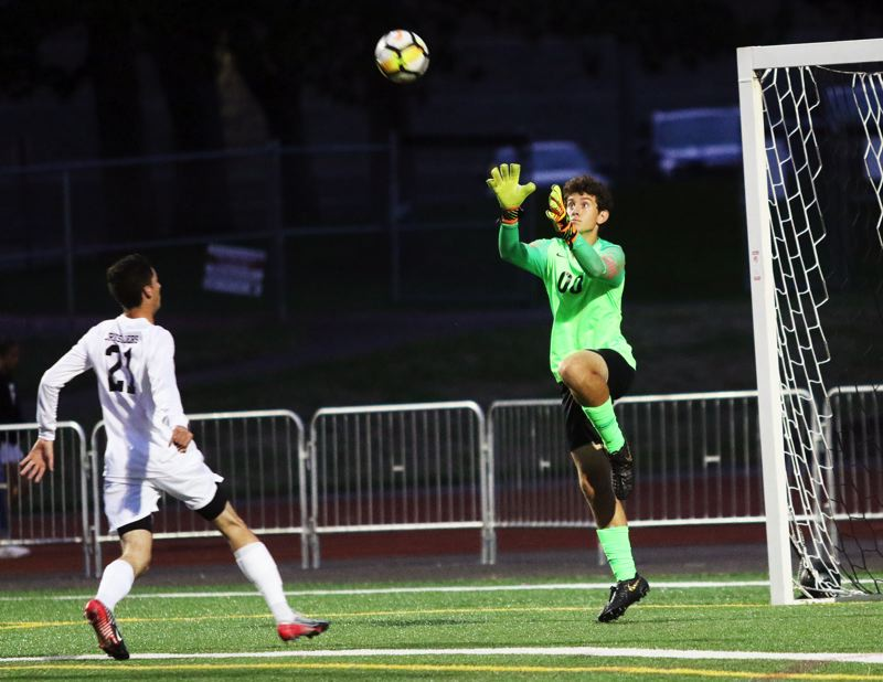 PMG PHOTO: DAN BROOD - Sherwood High School junior goalkeeper Kyle Stuckey (right) leaps to make a save in front of Jesuit senior Remington Grayson during last week's non-league match.