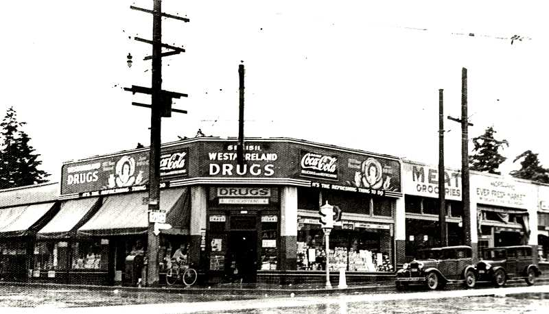 COURTESY OF THE CITY OF PORTLAND ARCHIVES - In this 1936 photo of the Bybee-Milwaukie intersection, we see the Westmoreland Drug Company where Starbucks stands now, at 7001 S.E. Milwaukie Avenue, with a very early two-light sidewalk pedestal traffic signal - and, next to it, a white porcelain street water fountain, and not the brass replica fountain that sits on that corner today.