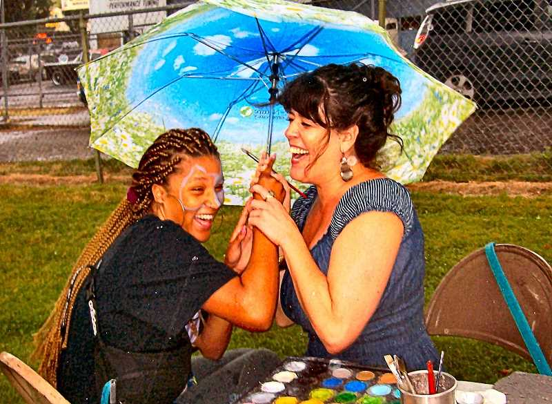 RITA A. LEONARD - Face painter Sophia Marie (at right) finished painting a customer under an umbrella, when midafternoon sprinkles appeared in Brooklyn Park.
